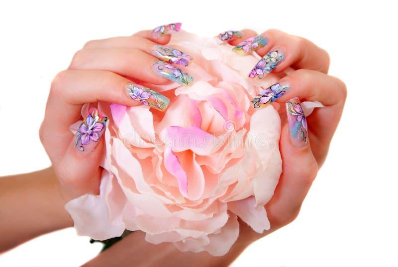 Mãos fêmeas bonitas com tratamento de mãos da arte do prego fotos de stock