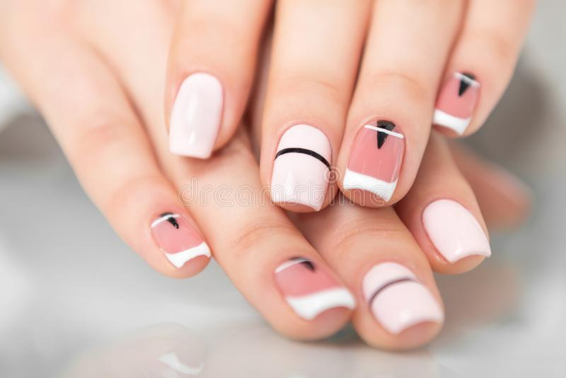Mãos fêmeas bonitas com um tratamento de mãos elegante Projeto geométrico dos pregos imagens de stock royalty free