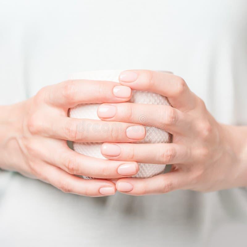 Mãos fêmeas bonitas que guardam o copo branco Tratamento de mãos com verniz para as unhas nude fotos de stock royalty free
