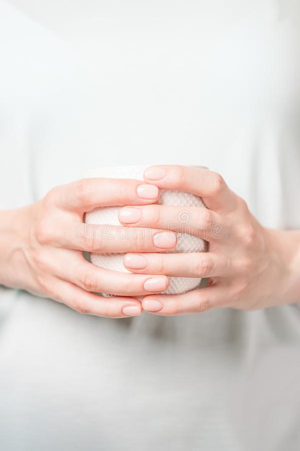 Mãos fêmeas bonitas que guardam o copo branco Tratamento de mãos com verniz para as unhas nude Copie o espa?o fotografia de stock royalty free