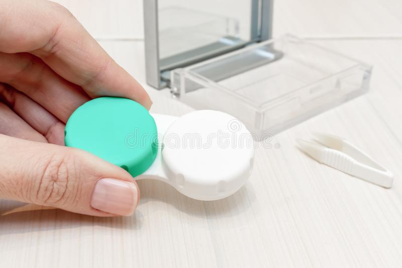 Mãos fêmeas colhidas que guardam um recipiente das lentes de contato imagens de stock