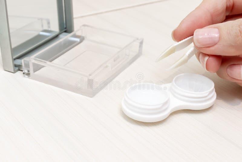 Mãos fêmeas colhidas que tomam lentes de contato fora de um recipiente imagem de stock royalty free