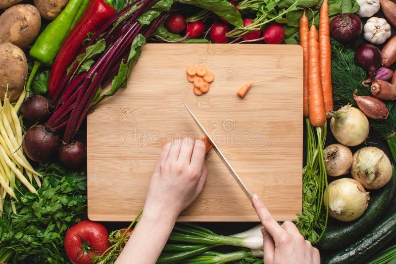 Mãos fêmeas com cozinheiro chefe Knife Cutting Carrot na placa de madeira fotografia de stock
