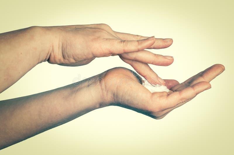 Mãos fêmeas com creme no branco - estilo retro imagens de stock royalty free
