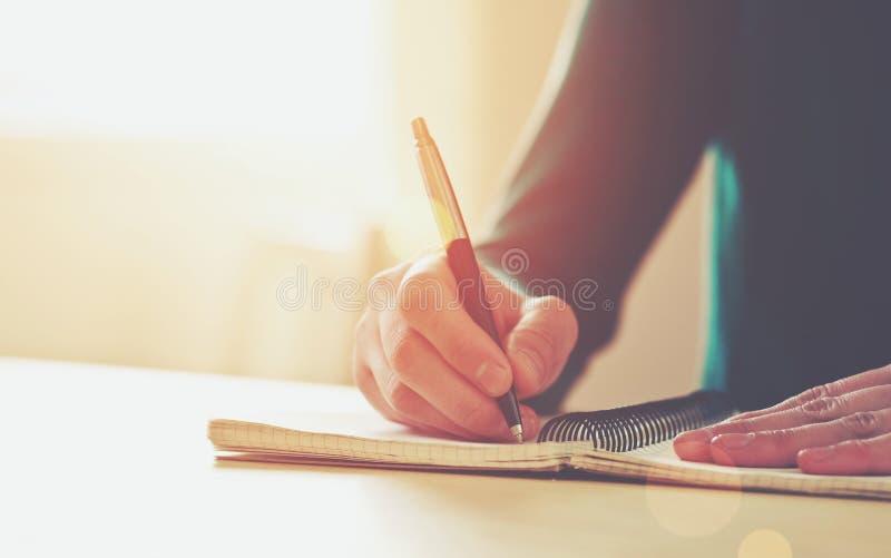 Mãos fêmeas com escrita da pena imagens de stock royalty free