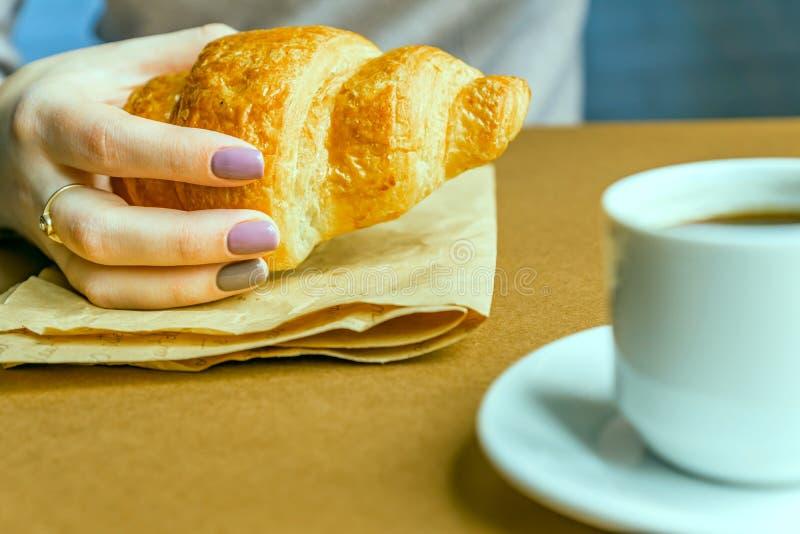 Mãos fêmeas com o croissant da terra arrendada do tratamento de mãos Café da manhã no estilo francês imagens de stock royalty free