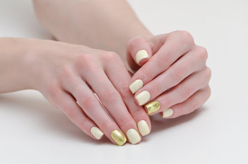 Mãos fêmeas com o tratamento de mãos, amarelo com a coberta do ouro dos pregos Fundo branco imagem de stock