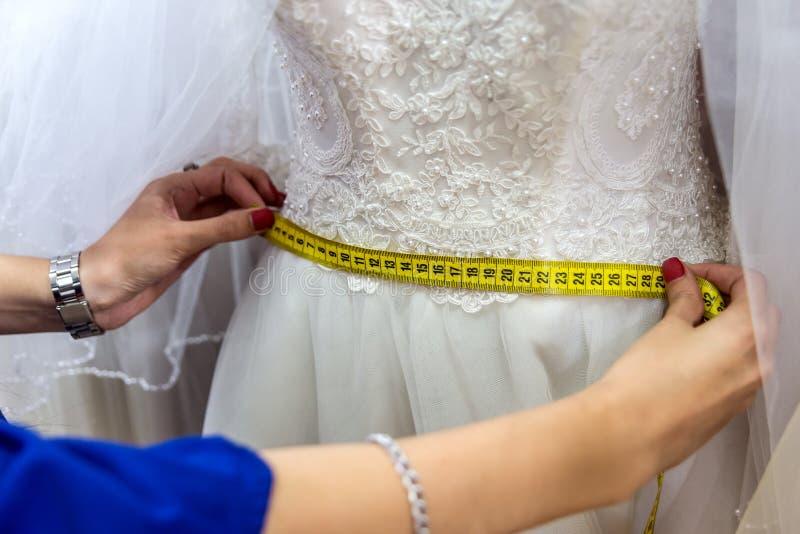 Mãos fêmeas com o vestido de medição da fita e de casamento fotografia de stock royalty free