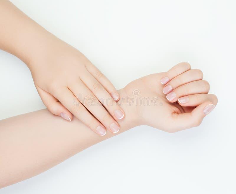 Mãos fêmeas com os pregos bonitos no fundo branco foto de stock royalty free
