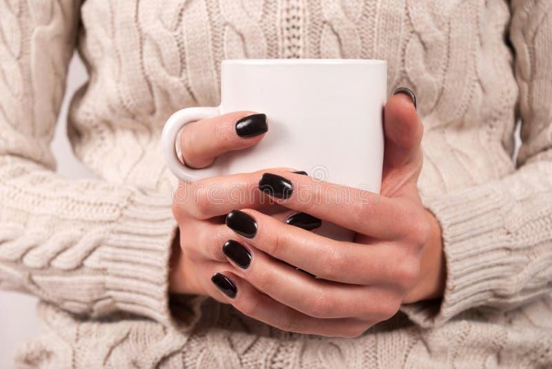 Mãos fêmeas com pregos pretos e camiseta que guarda o copo do chá fotografia de stock