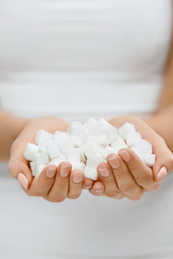 Mãos fêmeas com Sugar Cubes foto de stock