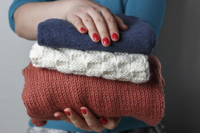 Mãos fêmeas com um tratamento de mãos vermelho que guarda uma pilha de coisas de lã feitas malha, vista dianteira, close-up foto de stock