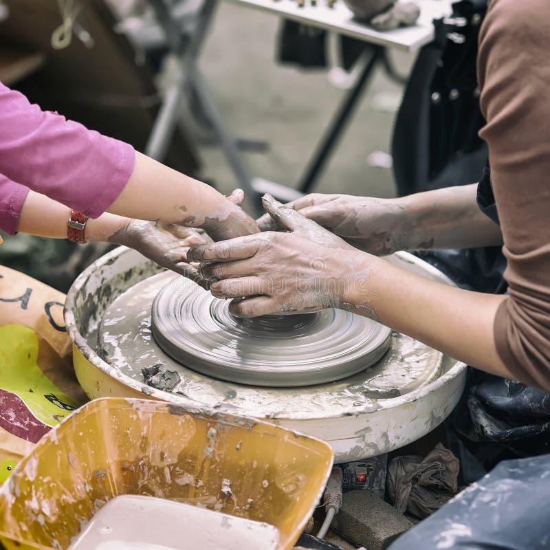 Mãos fêmeas das mãos do oleiro e da menina s O mestre ensina o estudante fazer o jarro na roda da cerâmica Classe mestra sobre foto de stock