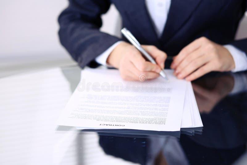 Mãos fêmeas desconhecidas com a pena sobre o documento do contrato Assinatura do acordo ou conceito do negócio imagens de stock