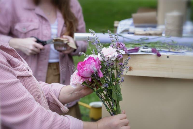 Mãos fêmeas do florista que criam o ramalhete moderno do verão de flores diferentes em cores roxas cor-de-rosa na loja imagens de stock royalty free