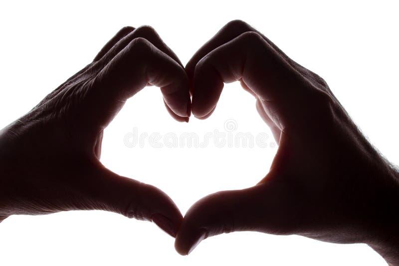 Mãos fêmeas e masculinas como um símbolo do coração imagens de stock