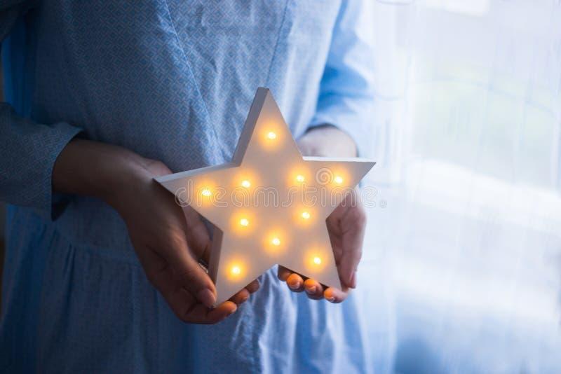 Mãos fêmeas macias do close up que guardam a estrela festiva de incandescência do diodo emissor de luz perto da janela na luz do  fotos de stock
