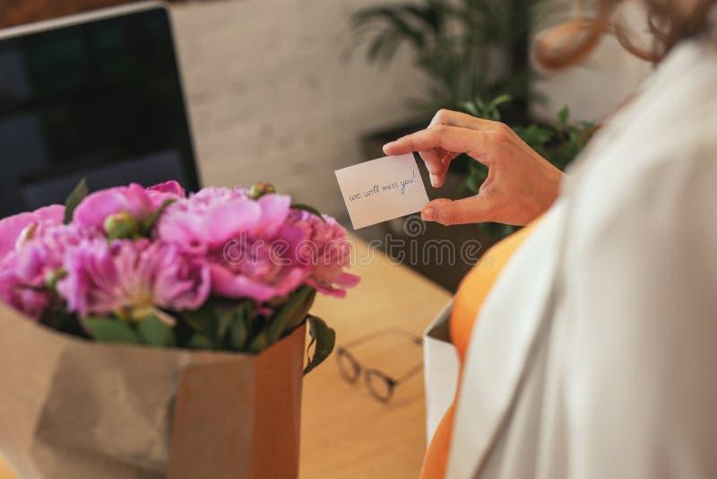 Mãos fêmeas macias que guardam o cartão atual foto de stock