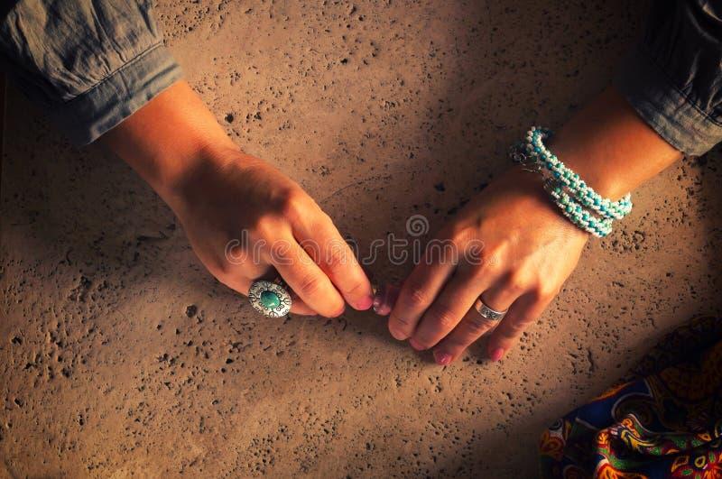 Mãos fêmeas morenos em uma tabela de mármore Verniz para as unhas da posse das mãos foto de stock royalty free