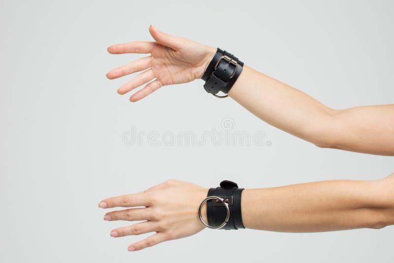 Mãos fêmeas nas algemas de couro no fundo cinzento Brinquedos do sexo imagem de stock