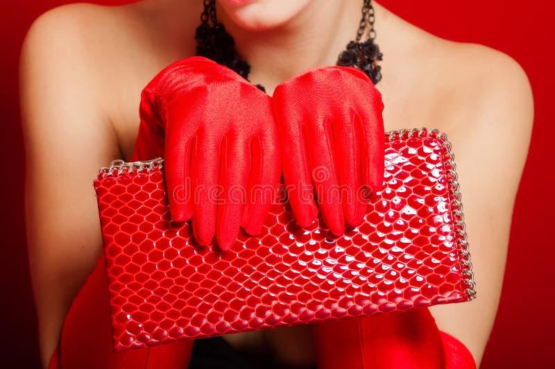 Mãos fêmeas nas luvas vermelhas que guardam uma embreagem vermelha imagem de stock
