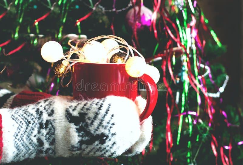 Mãos fêmeas nos mitenes que guardam a xícara de café vermelha grande com garla foto de stock