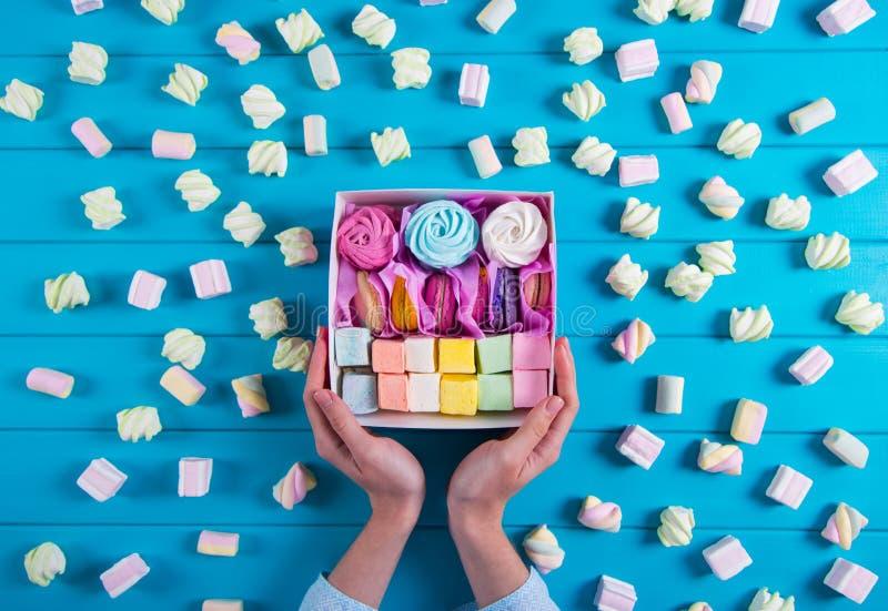 Mãos fêmeas novas que guardam a caixa completamente de bolinhos de amêndoa e do marshmallow coloridos com muito marshmallow difer fotos de stock