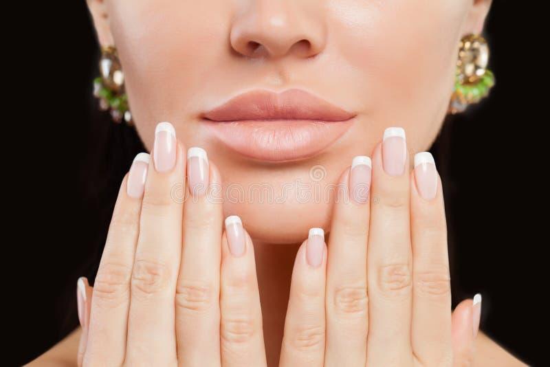 Mãos fêmeas perfeitas com pregos e os bordos manicured Tratamento de mãos francês e composição bege do batom fotografia de stock royalty free