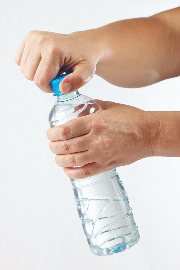 Mãos fêmeas que abrem uma garrafa da água mineral imagem de stock