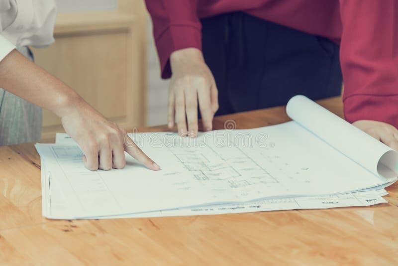 Mãos fêmeas que apontam no desenho do plano da casa fotografia de stock