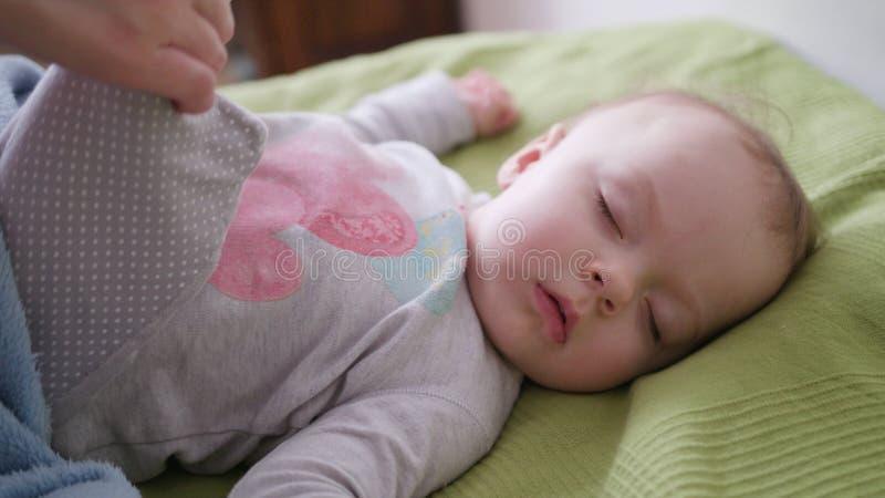 Mãos fêmeas que cobrem um bebê que encontra-se na cama foto de stock