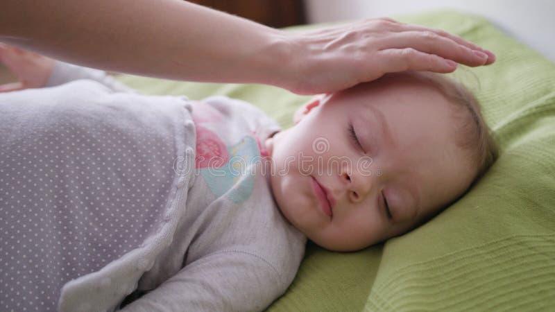 Mãos fêmeas que cobrem um bebê que encontra-se na cama imagens de stock royalty free