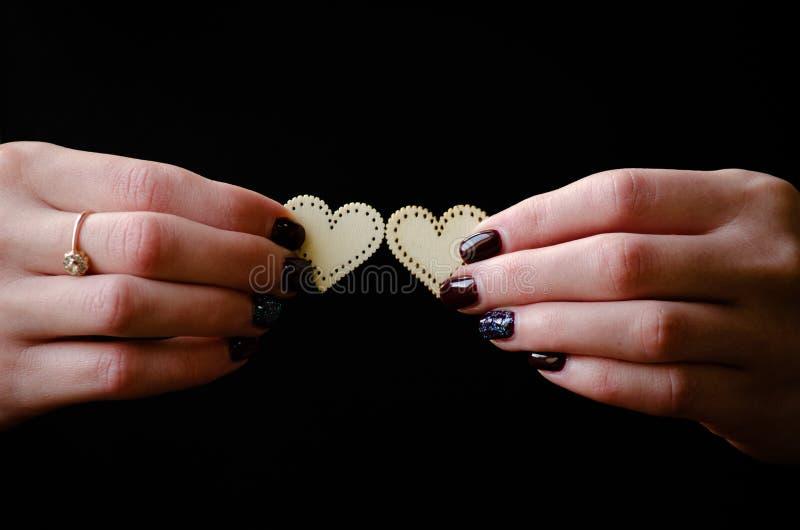 Mãos fêmeas que dão dois corações de madeira no fundo preto foto de stock