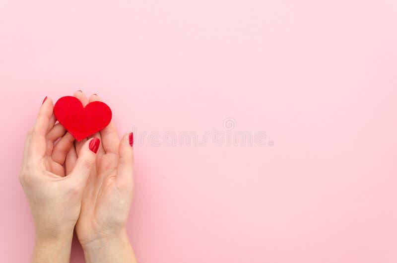 Mãos fêmeas que dão o coração vermelho Configuração lisa Coração vermelho do conceito do dia de Valentim nas mãos da mulher Copie fotos de stock