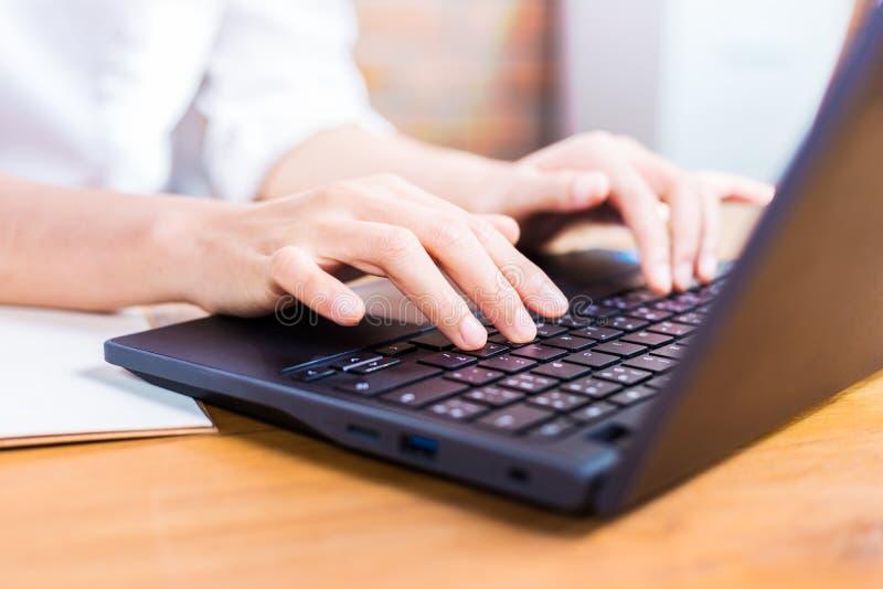 Mãos fêmeas que datilografam em seu computador fotografia de stock