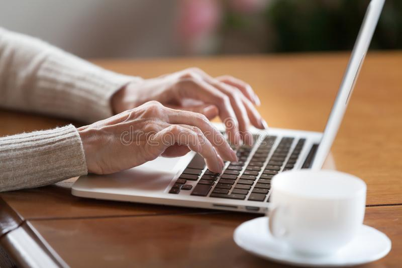 Mãos fêmeas que datilografam no teclado, mulher superior que trabalha no portátil foto de stock royalty free