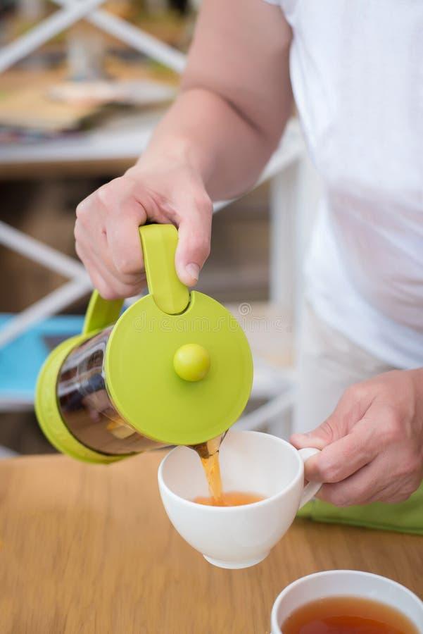 Mãos fêmeas que derramam o chá em um  de Ñ acima foto de stock