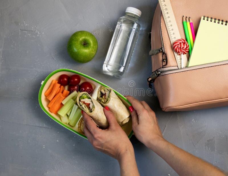 Mãos fêmeas que embalam o jantar na cesta de comida na tabela cinzenta imagem de stock royalty free