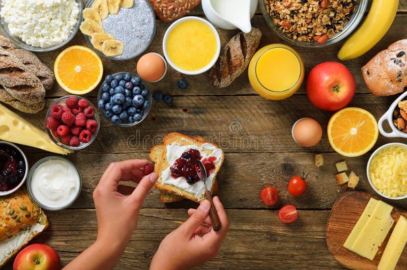 Mãos fêmeas que espalham a manteiga e o doce no pão Mulher que cozinha ingredientes saudáveis do café da manhã do café da manhã,  imagem de stock
