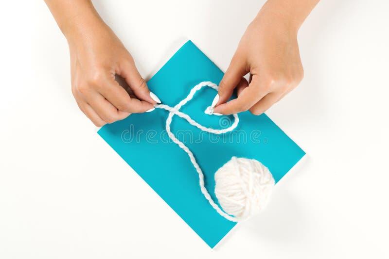 Mãos fêmeas que fazem o símbolo da forma do coração Lãs brancas do fio no papel azul Configuração lisa Ideia criativa com lãs bra foto de stock