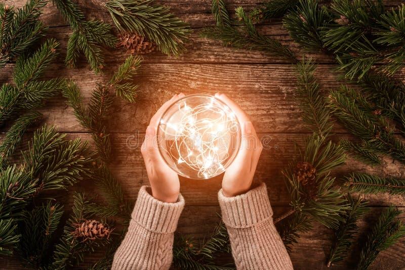Mãos fêmeas que guardam a bola de incandescência do Natal no fundo do feriado com ramos do abeto Cartão do Xmas e do ano novo fel fotos de stock