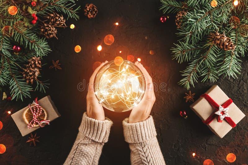 Mãos fêmeas que guardam a bola de incandescência do Natal no fundo do feriado com ramos do abeto, presentes fotografia de stock royalty free