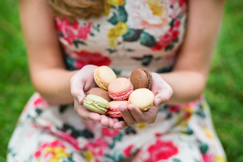 Mãos fêmeas que guardam bolinhos de amêndoa franceses coloridos imagens de stock