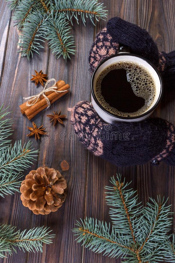 Mãos fêmeas que guardam a caneca de café do chocolate quente no fundo de madeira rústico com ramo de árvore do abeto do Natal, es fotografia de stock