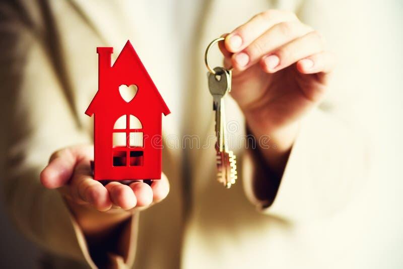 Mãos fêmeas que guardam a casa vermelha pequena e as chaves Oferta que do mediador imobiliário você abriga ou apartamento Seguro  imagem de stock royalty free