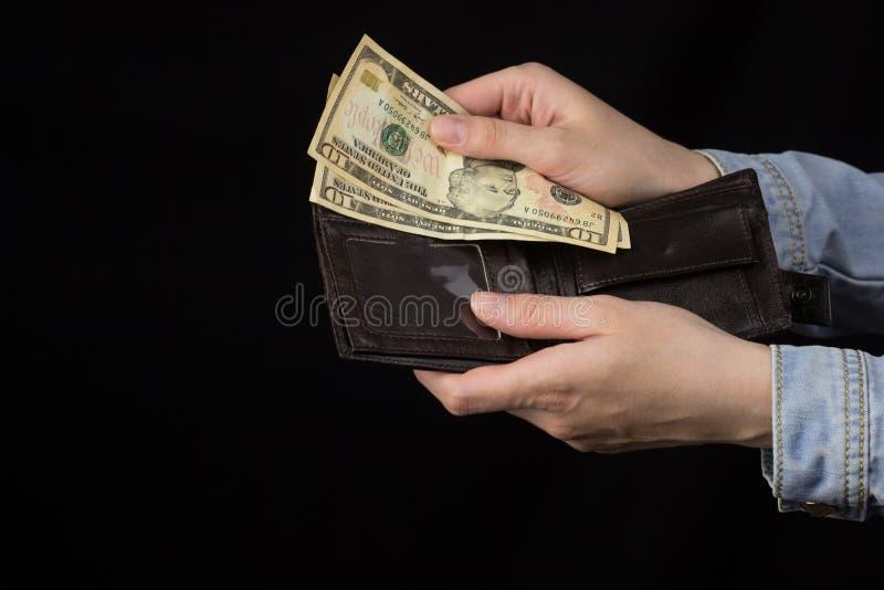 Mãos fêmeas que guardam dólares de uma bolsa em um fundo preto, close-up imagens de stock