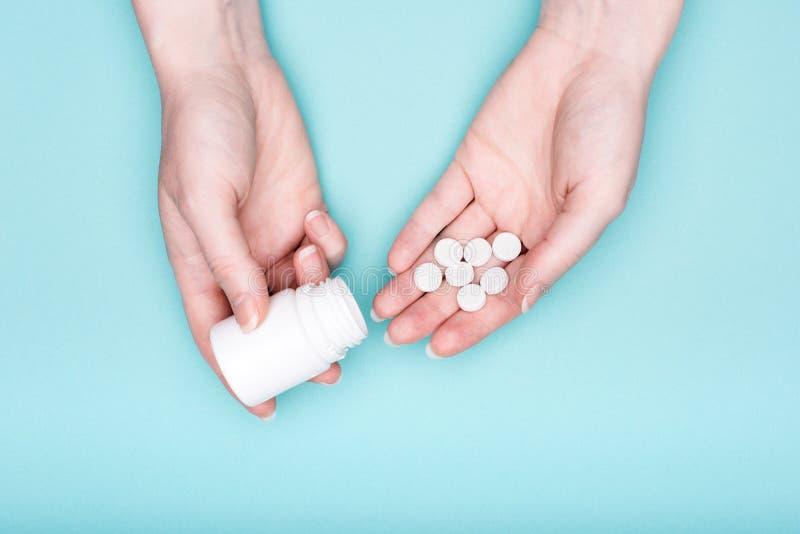 Mãos fêmeas que guardam a garrafa da medicamentação e os comprimidos brancos sobre o fundo azul pastel Medicamentação de tomada p fotos de stock royalty free
