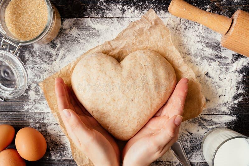 Mãos fêmeas que guardam a massa na opinião superior da forma do coração Ingredientes do cozimento na tabela de madeira escura imagem de stock royalty free