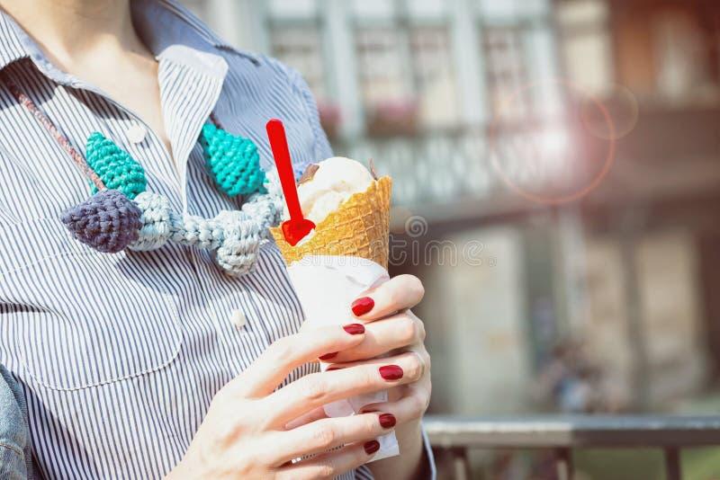 Mãos fêmeas que guardam o ar livre do gelado do cone efeito do brilho do sol imagem de stock royalty free