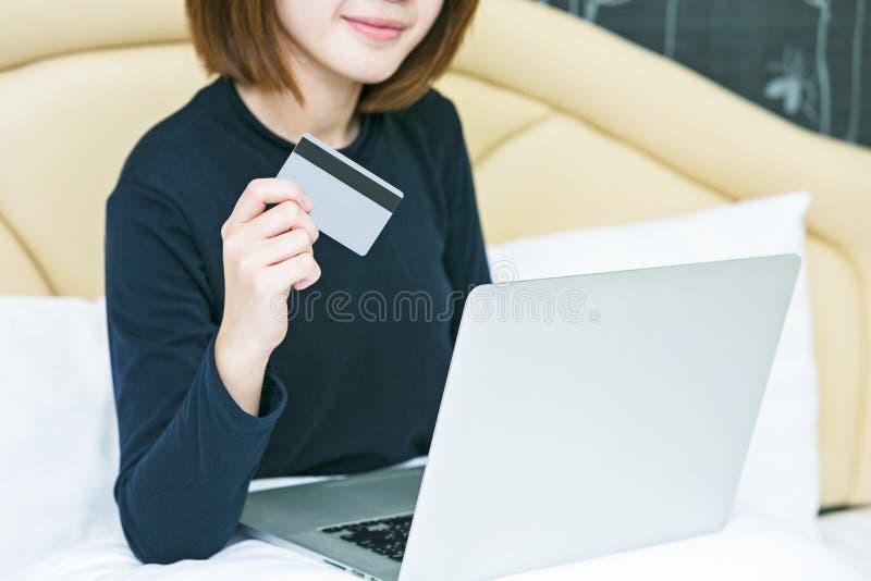 Mãos fêmeas que guardam o cartão de crédito e que usam o portátil Shoppi em linha foto de stock